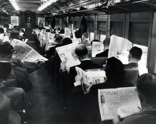 homens lendo jornal dentro do trem 01