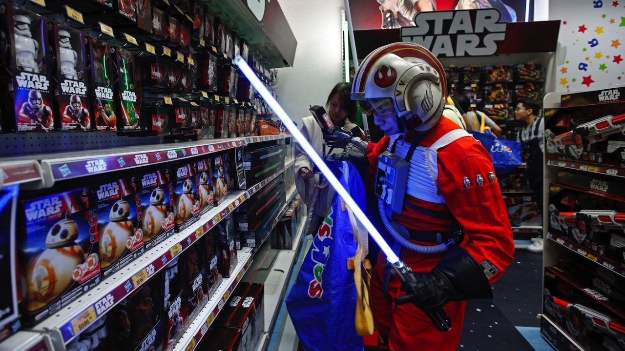 """A fan dressed as a Star Wars character shops at a toy store at the midnight in Hong Kong, Friday, Sept. 4, 2015 as part of the global event called """"Force Friday"""" to release new Star Wars toys and other merchandise of the new movie """"Star Wars: The Force Awakens"""". (AP Photo/Kin Cheung)"""