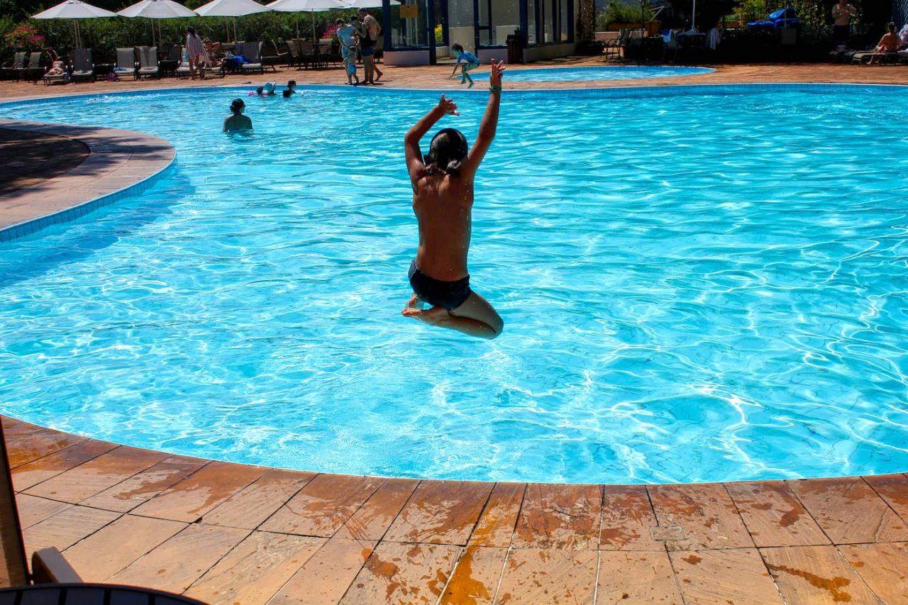 Menino pulando na piscina